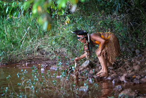 An Indigenous woman from the Pataxo Ha-ha-hae tribe holds up a dead fish near Paraopeba river