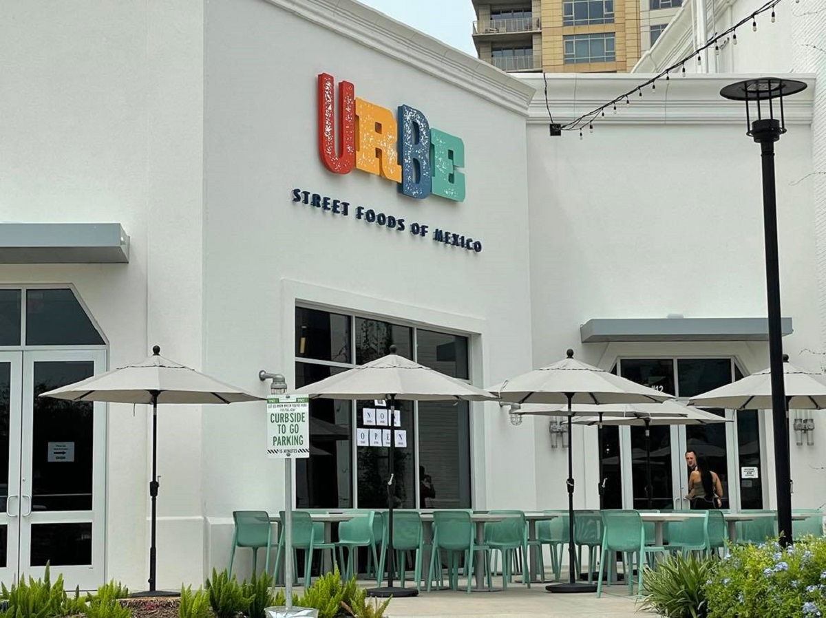 """storefront of restaurant with brightly colored letters """"URBE"""" and patio seating"""